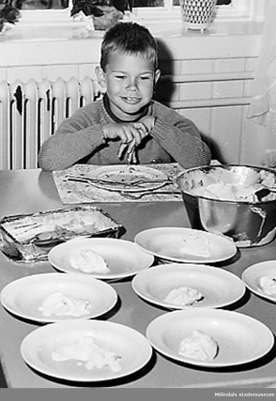 En pojke som sitter vid ett dukat matbord. Holtermanska daghemmet 1953.