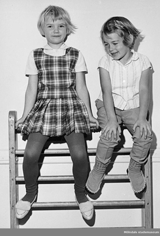 Två flickor sitter högst upp på en ribbstege vid Holtermanska daghemmet 1953.
