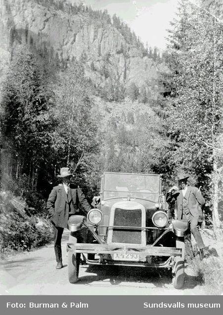Två män vid bil.