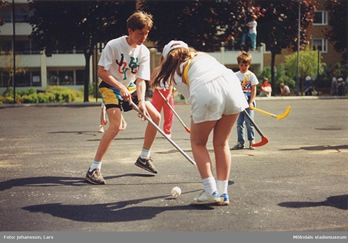 En av bostadsrättsföreningen Tegens gårdsfester i Kvarteret Pinnharven 1989. Man hade bland annat korvservering, poängpromenad, spel, tävlingar, sång- och musikunderhållning m.m. Här spelar ungdomar bandy på en asfalterad plan.