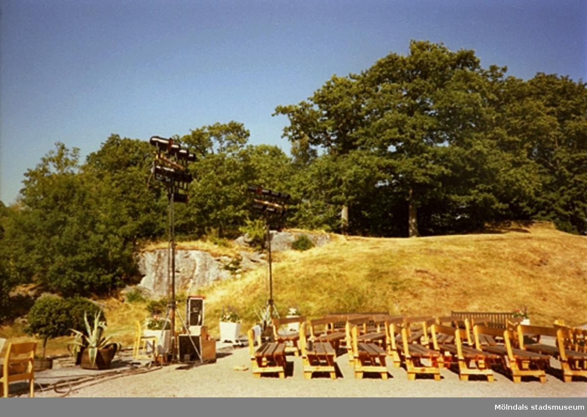 Uppställda strålkastare och ljudanläggning som står på en låda. Parksoffor står uppradade i parken med skogen omkring.