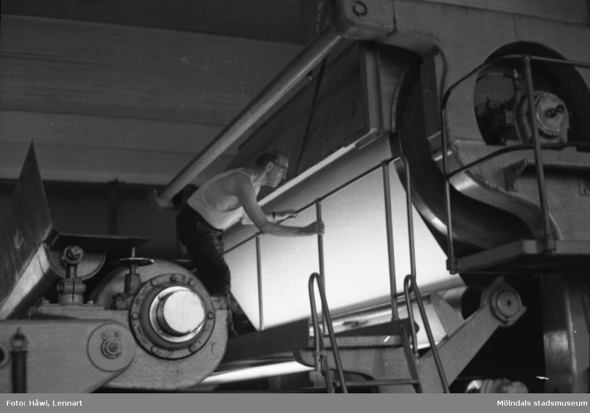Man i arbete vid maskin, KM 2. Övergången mellan press och torkparti. Byggnad 6. Papyrus i Mölndal, hösten 1970.