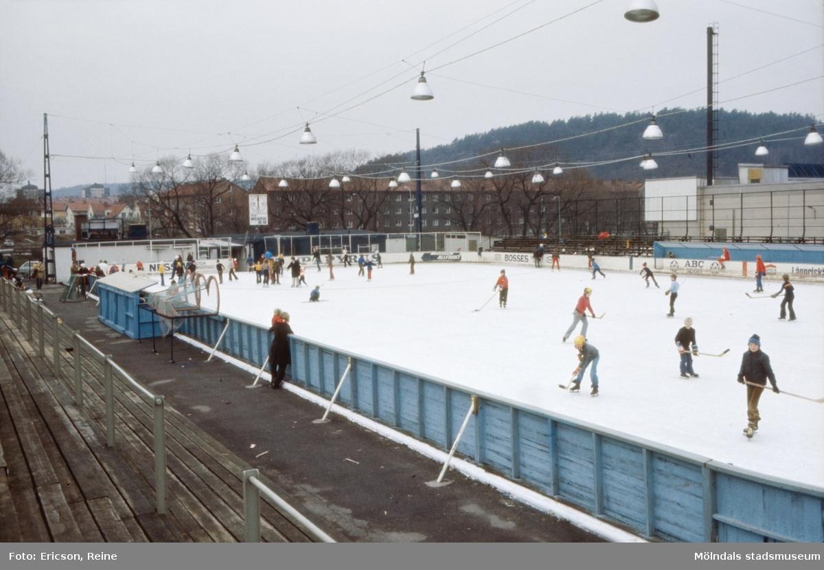 """Konstisbanan i Mölndal 1973. Invigdes hösten 1959. Den låg invid Mölndalsån mitt emot Centrallasarettet.  Den var mycket uppskattad av ungdomen i bygden.  Här kunde skolungdomen träna på skridskor och spela ishockeymatcher. Under högsäsong var isbanan fulltecknad på kvällarna vid idrottsföreningarnas tävlingsmatcher.  Dessutom uppläts isbanan till allmänheten för motions- och nöjesåkning.  Isbanan var uppbyggd på en jämn bädd av sand och grus, på vilken ett invecklat rörsystem låg. Rören vilade på ett underlag av """"syllar"""" eller ribbor över hela planbädden. Mellan rören var ett avstånd på cirka 10 cm. Över detta var det påfyllt med grus mellan rören, så att dessa nästan täckes.  För att frysa själva istäcket däröver fordrades att underlaget först frusits ned och fått """"tjäle"""".  En kylvätska, bestående av ammoniak, pumpades in i rörsystemet. Kylvätskan höll vid utpumpningen en temperatur av cirka -20 grader. När kylvätskan återkom från systemet hade den en temperatur av cirka -5 grader. Vatten spolades då över bädden och frysningen av istäcket började. Istäcket var ca 5 cm tjockt.  Kylvätskan  cirkulerade sedan oavbrutet i rörledningarna för att hålla istäcket lagom fruset.  För att undvika sprickbildningar i isen måste kylvätskans temperatur noggrant varieras, allt eftersom den omgivande luftens temperatur steg eller föll.  1978 flyttades Mölndals gamla isbana till Kållereds sportanläggning. Den började återigen att användas där 1978-1979."""
