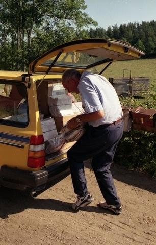 Lantbrevbärare Reinhold Andersson vid sin brevbärarbil på väg ut med dagens lantbrevbäring. Tillhör en dokumentation av en lantbrevbärare i trakten av Valdermarsvik av fotograf Ove Kaneberg.