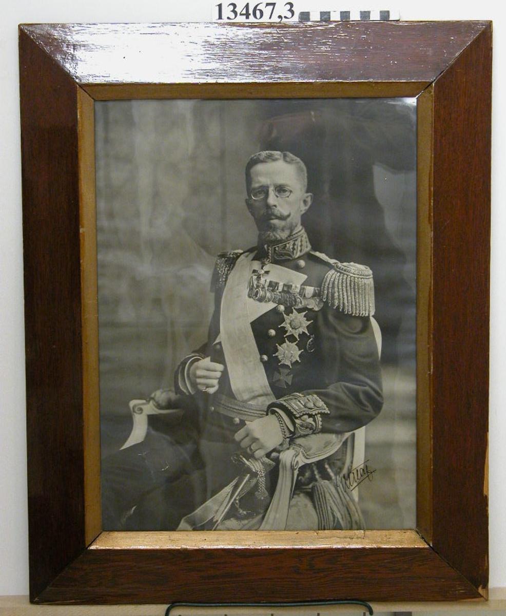 Fotografi inom glas och ram. Porträtt av H.M. konung Gustaf V. Har tillhört maskinisternas uomäss på pb Oscar II.