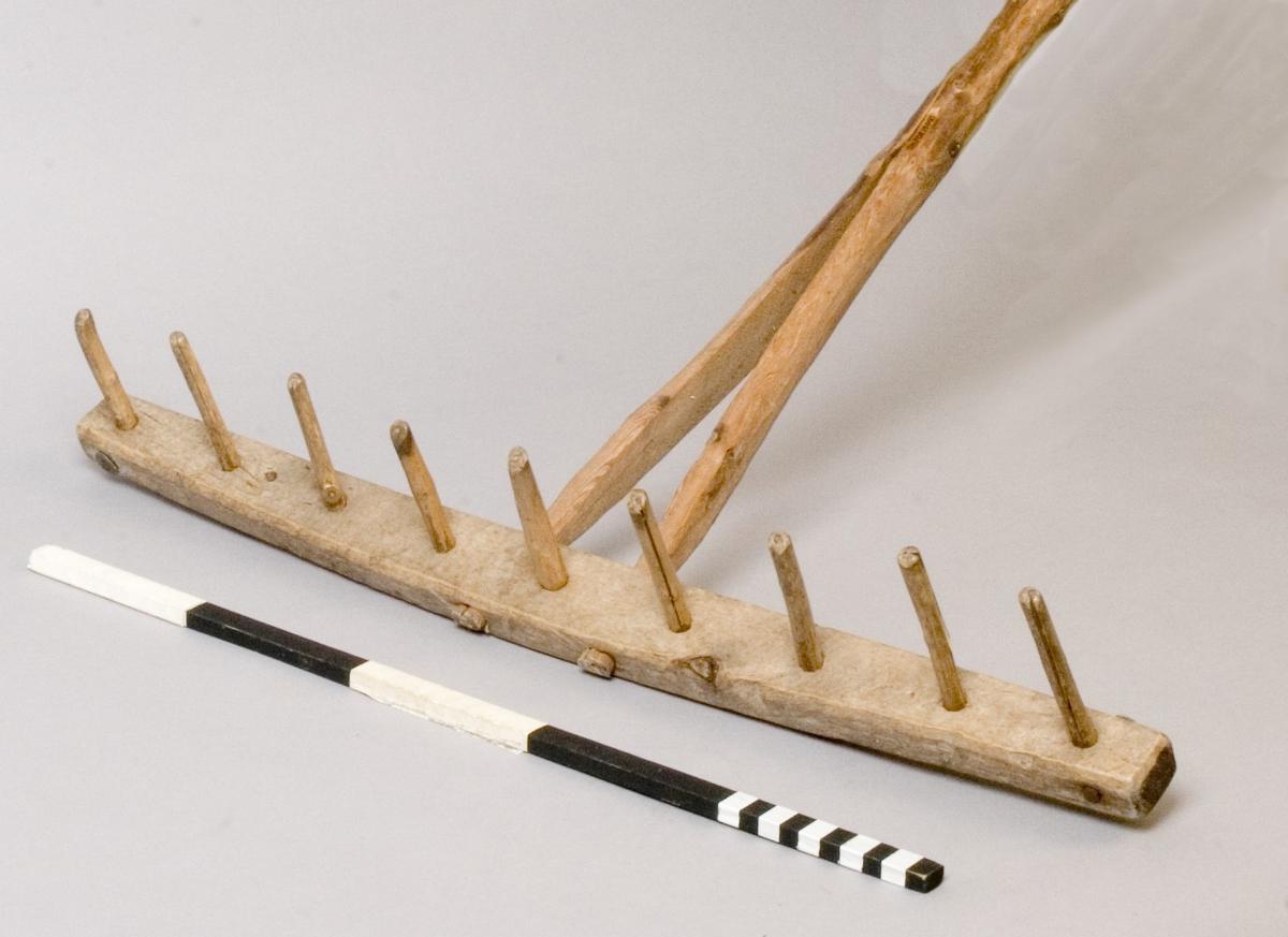 Räfsa, handgjord. Modell där nedre delen av handtaget, c:a 330 mm, är kluven och infattad i räfskammen. Förstärkt vid klovets början med genomgående spik och bricka. Även räfskammens ändar är förstärkta på samma vis. Nio pinnar, c:a 85 mm långa.