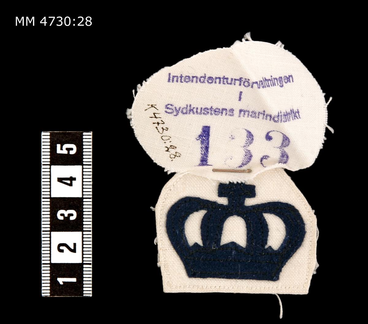 Yrkesbeteckning, krona. Av blått kläde på vit botten. För underofficerskorpral, senare flaggkorpral.