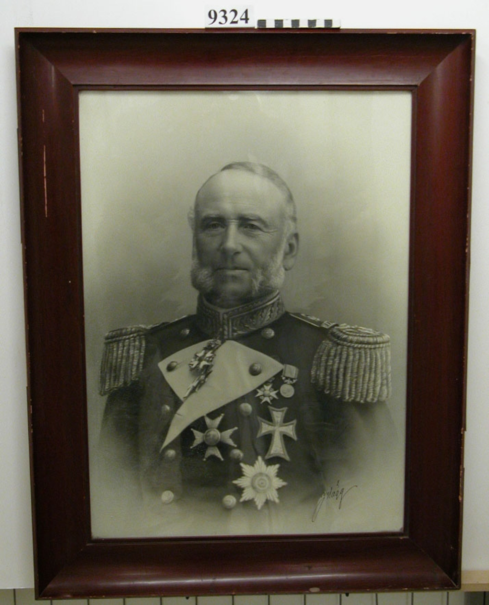 Fotografi inom glas och ram, av trä, brunbetsad. visar amiral J. Hägg i uniform. Märkt med amiralens egen namnteckning: J. Hägg.