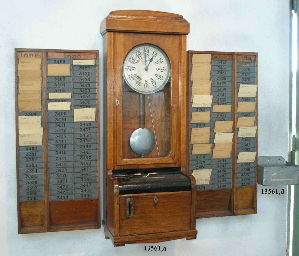 Stämpelklocka-, tidkontroll. I låda av ekträ, ljusgul. Urverket placerat i övre delen, täckt med glas, i nedre delen stämpelapparaten.