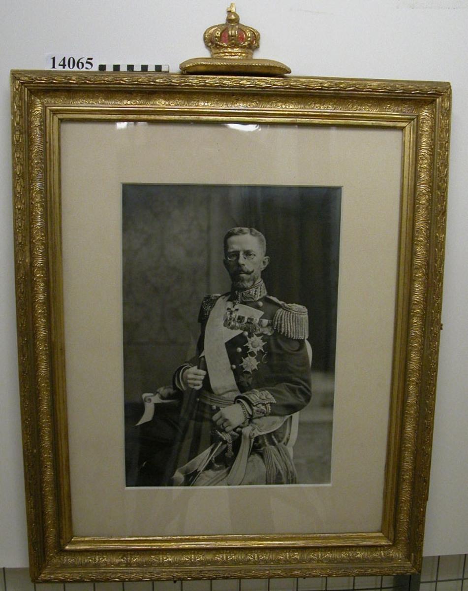 Fotografi inom glas och ram, ramen guldfärgad och krönt med kunglig krona, fotot infattat i gråvit passepartout. Motiv: H.M. Konung Gustaf V sittande på en stol iförd amiralsuniform M/78 parad.