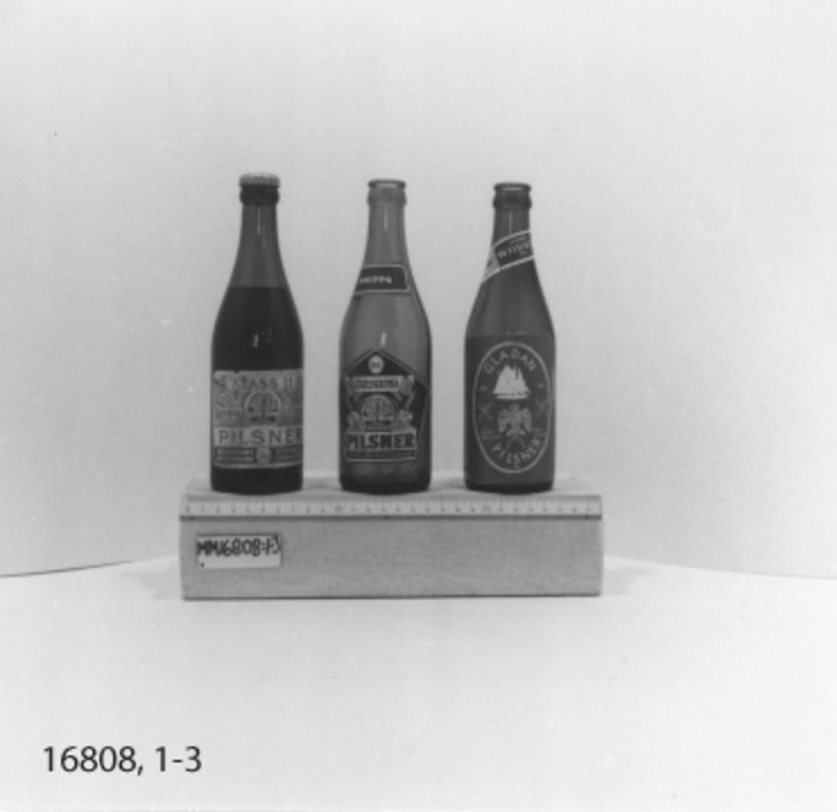 """1 flaska, 33 cl, i brunt glas med kapsyl av vitmetall. Rektangulär etikett, vit botten, tryck i grönt och guld med text= """"Klass II Pilsner Aktiebolaget förenade bryggerierna i Carlskrona"""". Fabriksmärke bestående av oval med träd i kronan bokstäverna T och B i kombination. Även mindre oval med bokstäverna T och B i kombination inom ett G. Veteax och banderoller. I botten H 49 och tre blommor. Pilsner kvar i den oöppnade flaskan."""