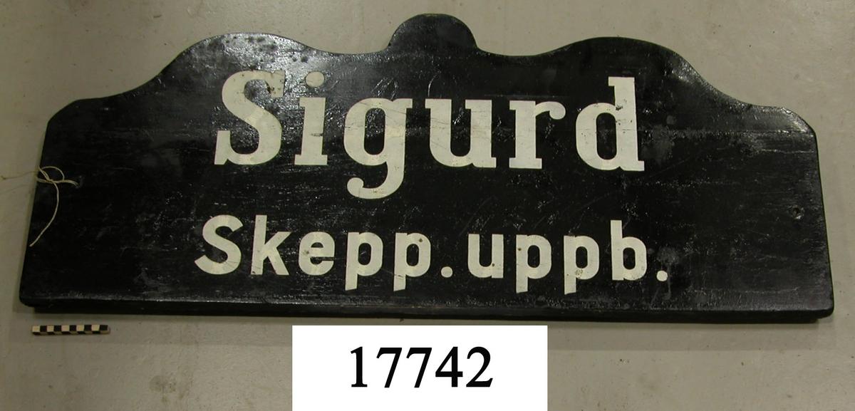 """Rekangulär skylt, ovansidan sågad i tre bågar, svart målad. Vit schablonmålad text: """" Sigurd Skepp. uppb. """", svartmålad baksida."""