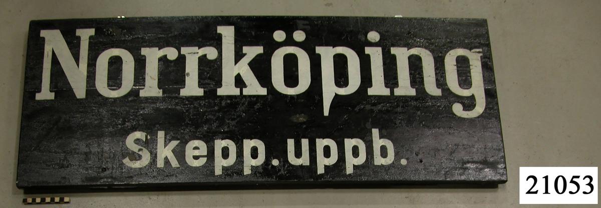 """Skylt av träplankor, sammanfästa med brädor på baksidan. Svartmålade, vit schablonmålad text: """"Norrköping Skepp. uppb."""""""