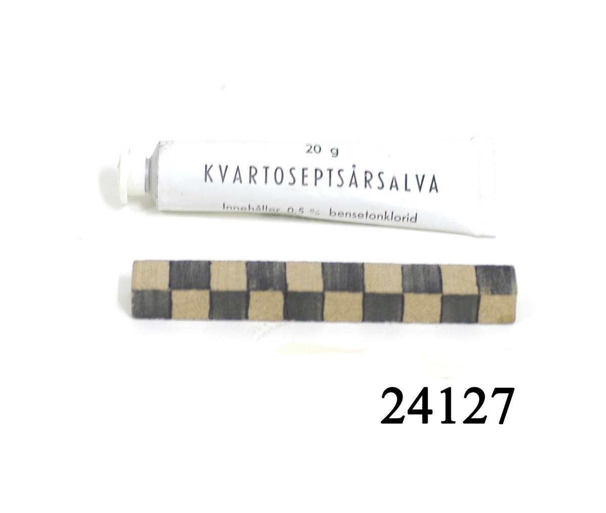 "Vit tub av metall, vit skruvkork av plast. På tuben svart text: ""20 g Kvartoseptsårsalva Innehåller 0,5 % bensetonklorid. MILITÄRAPOTEKET STOCKHOLM, 56""."