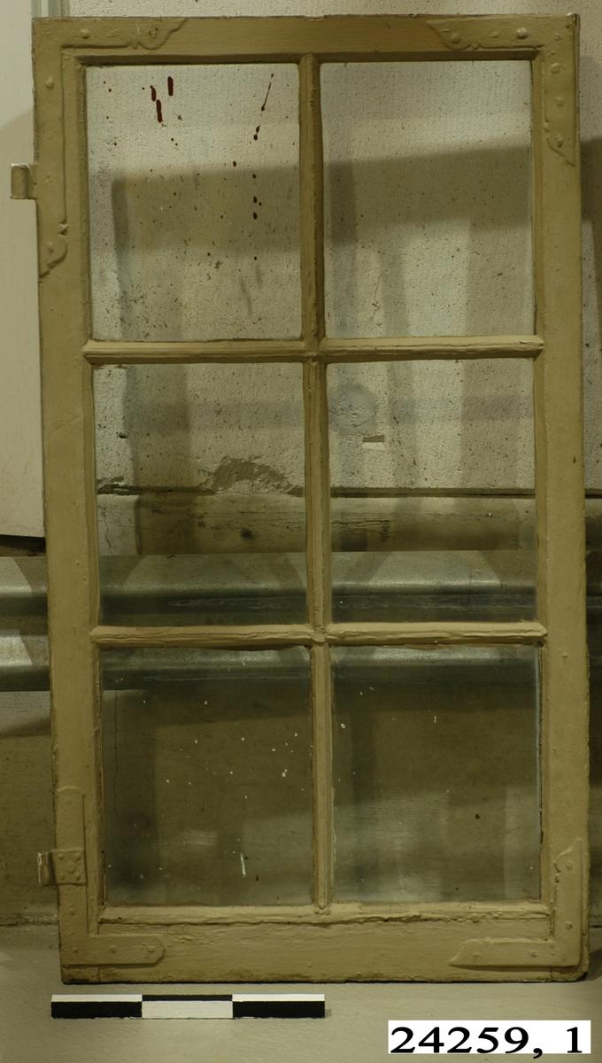 Spröjsat fönster med sex fönster inom brunmålad ram av trä. Vitmålad insida. På insidan sitter en hasp.