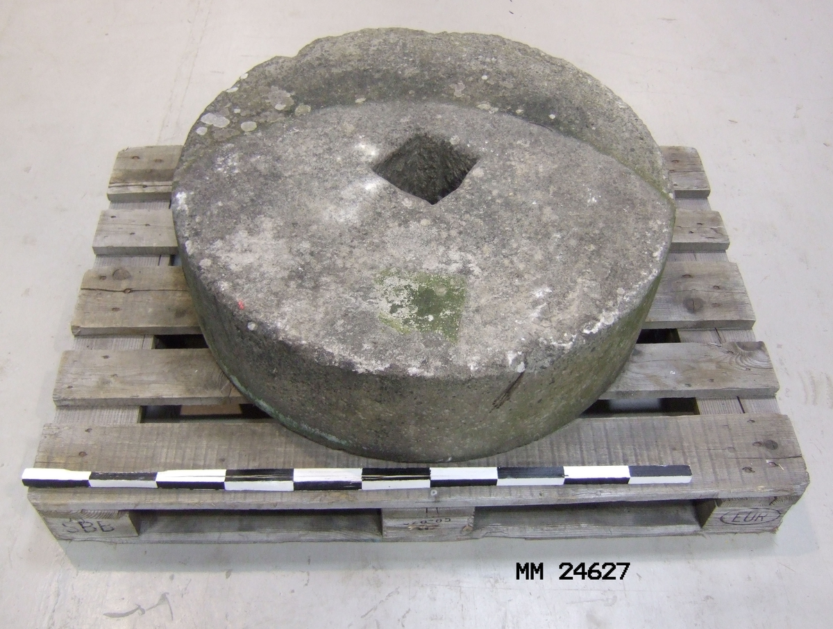 Slipsten, hjulformat, förmodligen av sandsten. Fyrkantigt hål i mitten. Ingen färg.