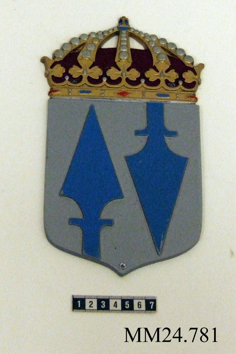 Vapensköld av metall. I fält av silver en uppkommande och en nedkommande spjutspets, båda blå. Kröns av kungakrona.