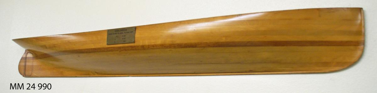 """Halvmodell av fernissat trä föreställande Norska minbåten. Styrbordssida. På skrovets mitt finns mässingsbricka med texten: """"Norska minbåten, byggd år 1878 vid Kungl. flottans varf"""" samt diverse måttuppgifter."""