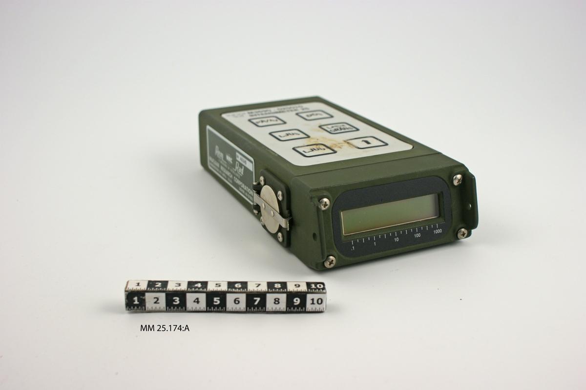 """Grön rektangulär låda. På framsidan finns en display med en skala som går från .1 till 1000. På ovansidan sitter en panel med sex knappar märkta """"PÅ/AV"""", """"DOS"""", """"LJUS"""", LARMGRÄNS"""", """"LJUD"""" och den sista med en uppåtriktad pil. Text ovanför panelen: """"M3690-025010 INTENSIMETER 25"""" samt en kronstämpel. PÅ ena långsidan av inteinsimetern sitter en lucka försedd med fjäderbelastat, runt lock i kromad metall. Bakom luckan finns en skylt med serienummer """"SN A0349"""". På skylten text som anger tillverkare och tillverkningsort. På baksidan sitter en batterilucka och jämte den ett uttag för att koppla in intensimetern till någon annan apparat. Uttaget försett med påskruvat kromat skyddslock med räfflade kanter. Skyddslocket fäst i intensimetern medelst en liten kedja."""