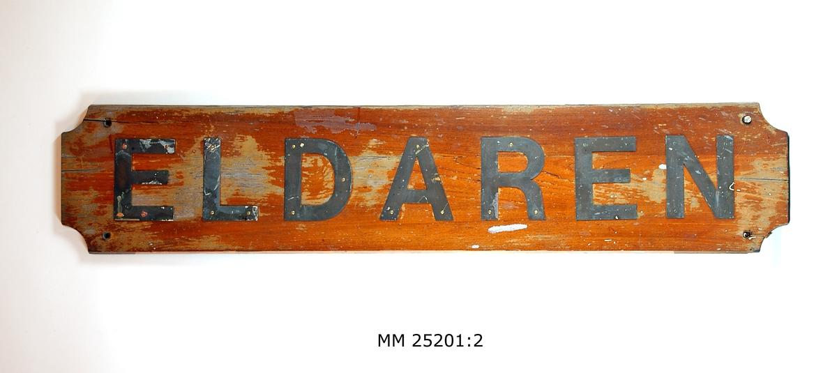 """Namnbräda av fernissad teak. Rektangulär träplatta med avhuggna hörn. Bokstäver av stål fastskruvade från framsidan, bildar namnet: """"Eldaren"""". Hål för upphängning."""