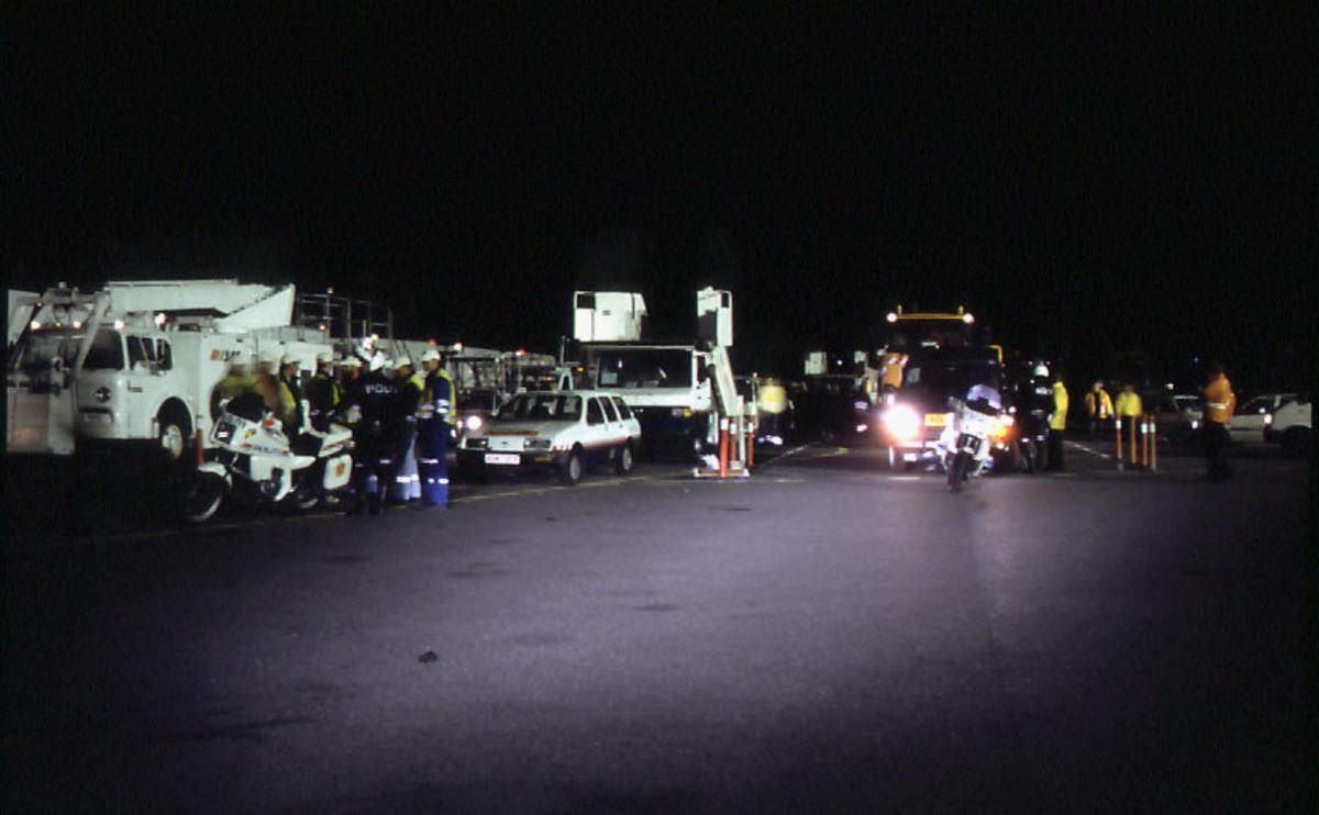 Lufthavn, flere personer, personell og politi, står foran flere kjøretøyer på en del av rullebanen.  Flere personer i bakgrunnen.