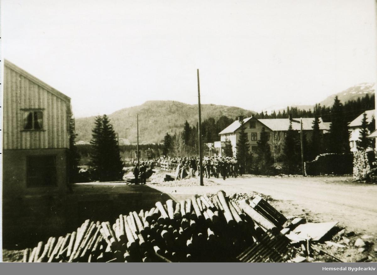 17. mai 1953 Barnetoget med Hemsedal Hornmusikk (Hornmusikken) i spissen marsjerer gjennom Trøym sentrum. Skogstad Hotell i bakgrunnen.