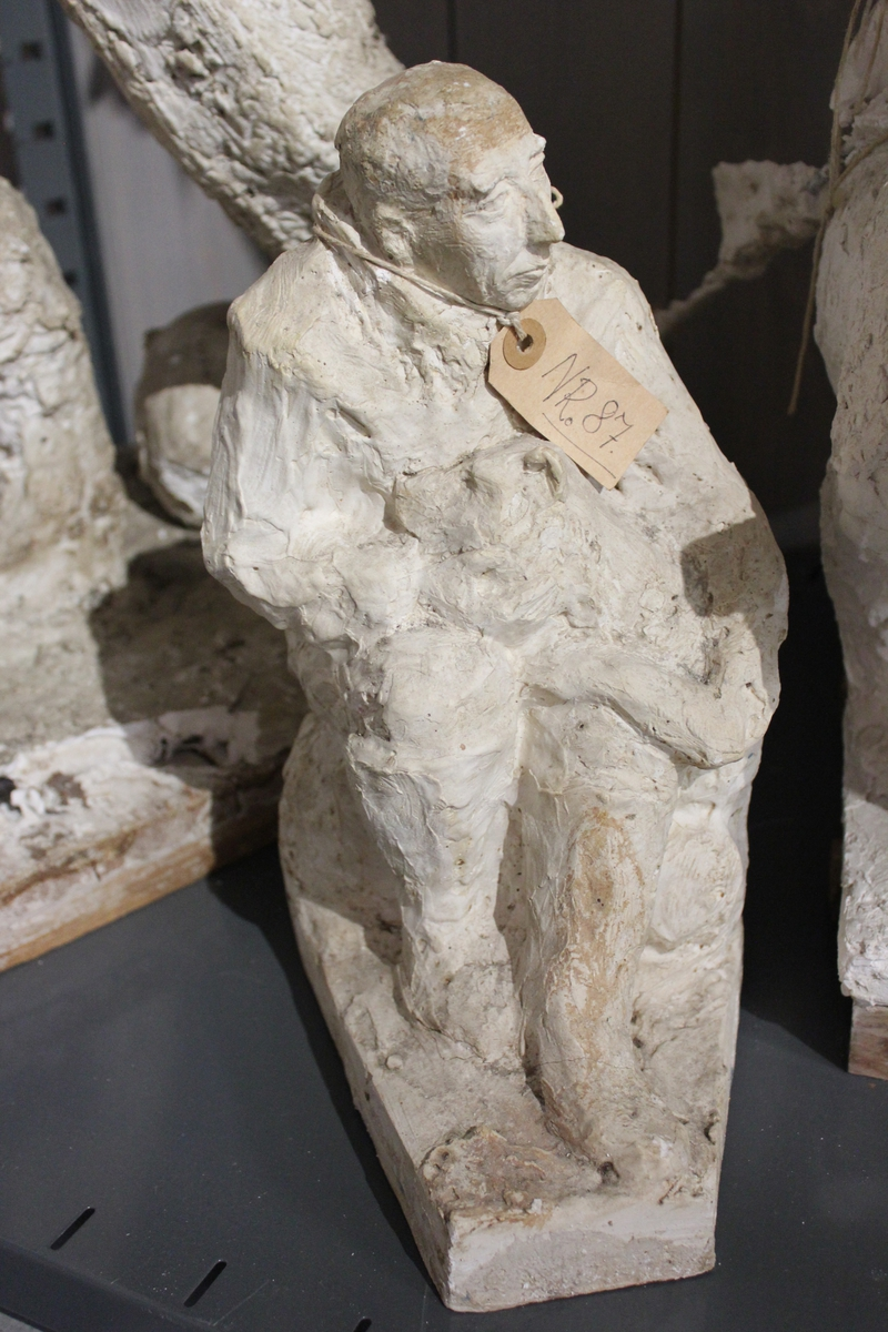 En skulptur i gips avRoald Amundsen med hund i fanget..