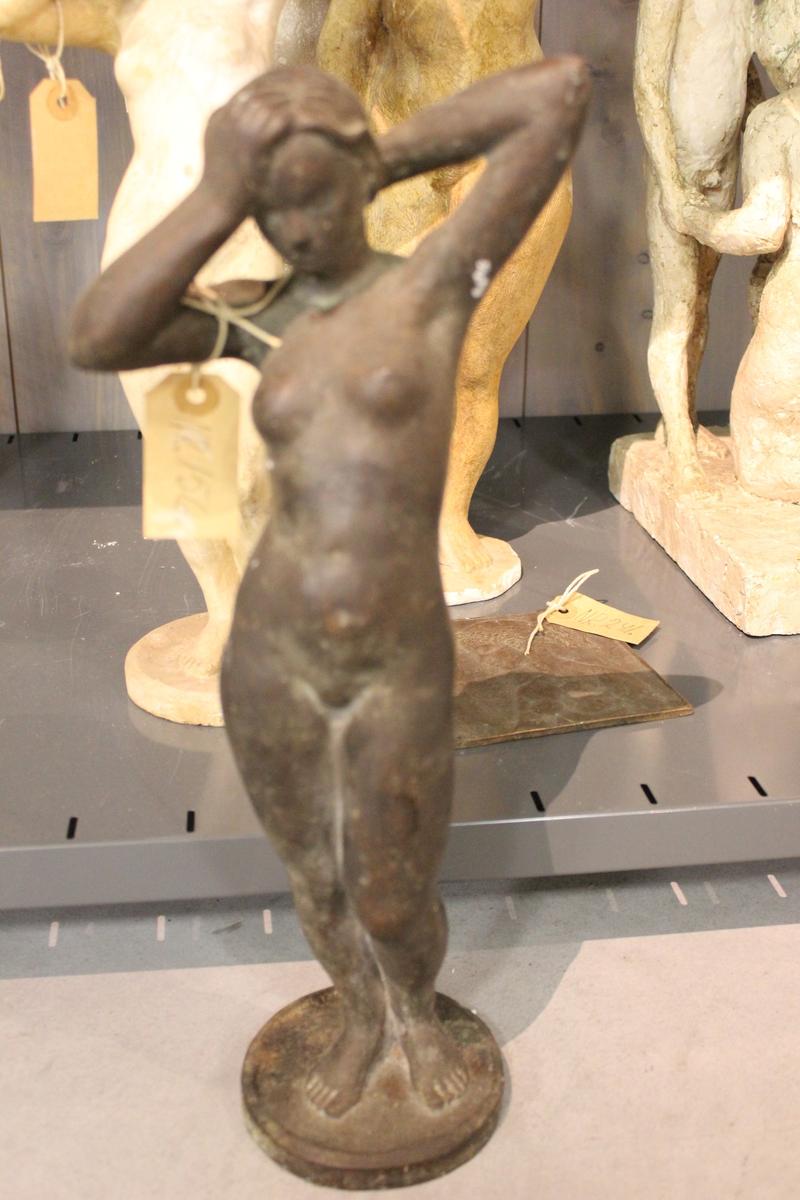 Skulptur i bronse av en kvinne som steller/ sveiper sitt hår.