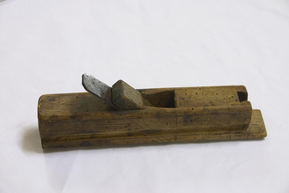 Trestykke med hull litt foran midten hvor tanna er festet gjennom med trebløy. Begge breisider listeformet. Under rund og litt lenger enn sidene.
