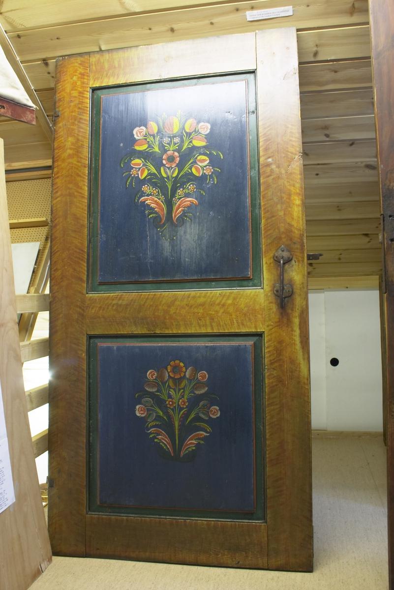 Rosemalt dør fra Vigmostad. Døra har to ruter som begge har grønn ramme med en tynn indre rød stripe. Bunn blå med rosemaling. Gul/brune kanter og mellom rammene. Håndsmidd håndtak. Rødmalt bakside. Døra er malt av rosemaleren Ole Goudsen Versland.