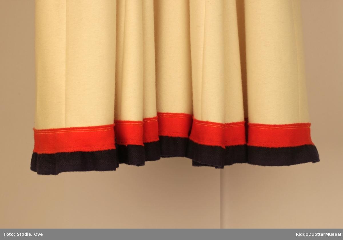 Kofta har påsydd dekorklede i rødt, blått og gult på bryst, skuldre, holbi, rygg og ermer. På fremre holbikant er det to tagger av gult klede som skiller seg ut .