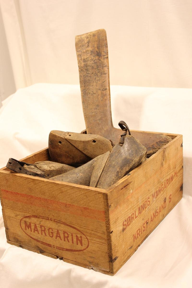 En trekasse med div. skoleister etc. Sørlands Margarin A/S, Kristiansand. Skoleisten ble brukt som form når skomakeren laget sko. 5 stk enkle tre-skomakerleister, en lang treform til langstøvler; et par skomakerleister, 2 trepinner, 1 tresømmerker, 1 fle, 2 metallesker med (insulating tape), 1 spaser-stokk. Dette ligger i en trekasse (Sørlands margarin A/S, Kristiansand) Tidl. merket nr 94A og B Skomakerleist tre. Form som en fot. 2 deler, der resten er egen del (B). Hull gjennom hælen, små nagler i tåa, lær ytterst. A: Mål L: 28 cm, B: 8,8 cm, H: 7 cm, B: Mål:l: 14 cm, B: 7,5 cm Giver: Elias L Stedjedalen Tidl merket nr 97 Skomakerleist tre, lær. De to delene er skrudd fast. Form som en fot. Lær naglet utenpå flere steder.Mål: L: 29 cm, B: 8,5 cm, H: 9,5 cm 23.7.1971 - Giver Borghild Roland Tidl merket 133 Skomakerleist tre. 2 deler; festet i hverandre med spiker og skrue. Overdelen likevel nesten løs. Form som en fot. Stykke av under hælen. Gjennom et hull i hælen er bundet en lærreim. Mål: L: 26 cm, B: 9 cm, H. 9,4 cm. Giver: Solveig Johannesen. Tidl. merket 134 Skomakerleist, tre, en del. Formet som en fot. Stykke avslått rund ogla. Lerreim fastspikra i hælen: Mål: L: 23,5 cm, B: 7,5 cm, H: 4,5 cm Giver: Solveig Johannesen Tidl merket nr 781 En treform til langstøvel Mål: l. 40,5 cm, B: 9,5 cm Gitt 23.10.1992 Reidar Eeg Tidl merket nr 98 1 stk - en del skomakerleist - tre formet som en fot, med et hull bak i hælen. M¨ål: l: 29 cm, B: 8,1 cm, H: 7,4 cm 1 par står også på skomakerverksted. Giver: Borghild Roland, 23.7.1971 Et par skomakerleist tre - 2deler festet i hverandre med spiker. Overdelen likevel nesten løs. Formet som en fot. Hull ene siden rist. Gjennom et hull i hælen henger tråd.  Mål: L: 26 cm, B: 8,5 cm, H: 6 cm Lengde tre-pinnene 14,5 og 12,5 cm Lengde tre-søm merker 16,5 cm Spaser-stokk - rund Lengde 79 cm, Dia topp: 2,5 cm