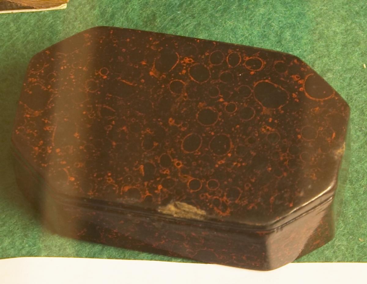 Liten eske/skrin med lokk. Den er avlang og har tre hjørner i hver ende. Sort/rød flammet farge på utsiden og sort innvendig.