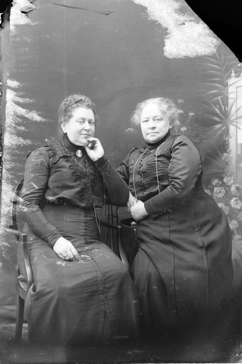 Studioportrett av to eldre kvinner.