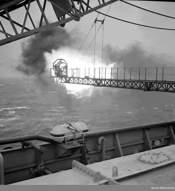 """To menn studerer en flammebom på boreplattformen """"Gulftide""""."""