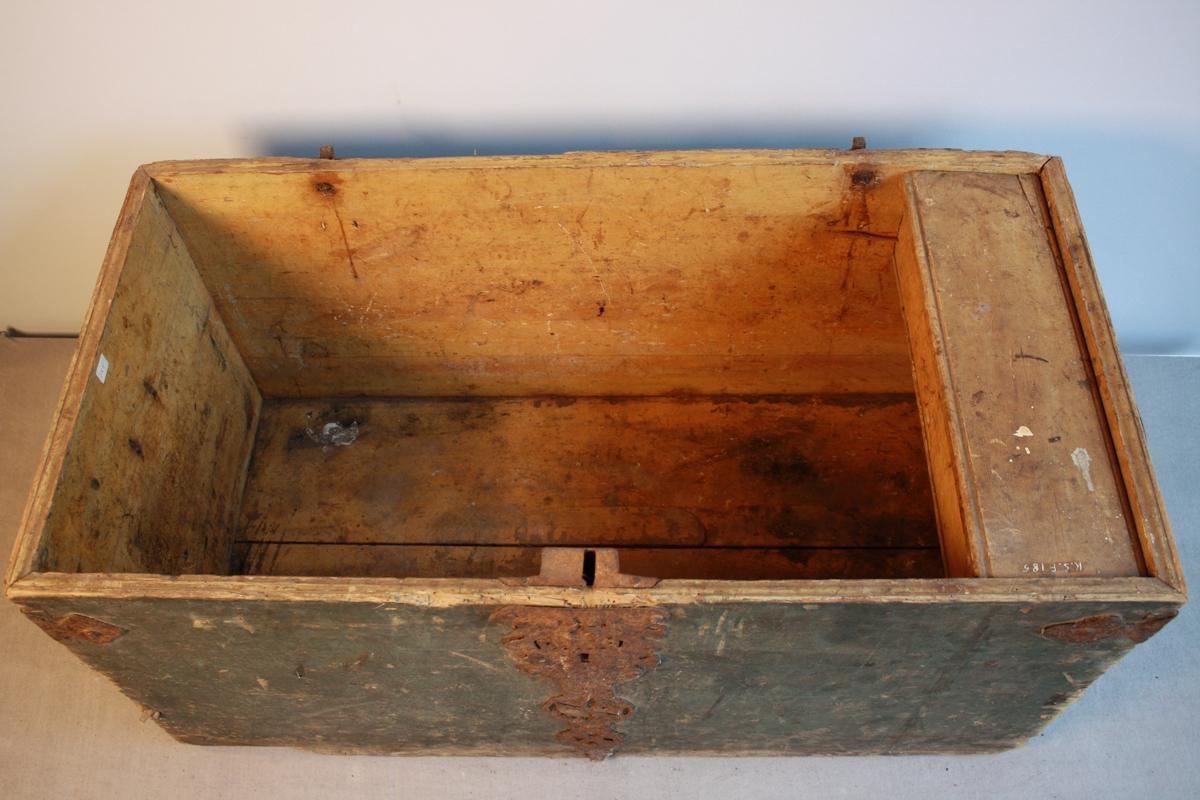 Grønmålt kiste med svakt bua lok. Jernbeslag over lås, lok og hjørner - spesielt mønster på jernbeslag over lås og lok. Hank av metall på begge sider. Botn og lok er skada av mott. Loket er laust. Sett saman med sinkink. Inni er kisti gulmålt og har ein leddik med lok.