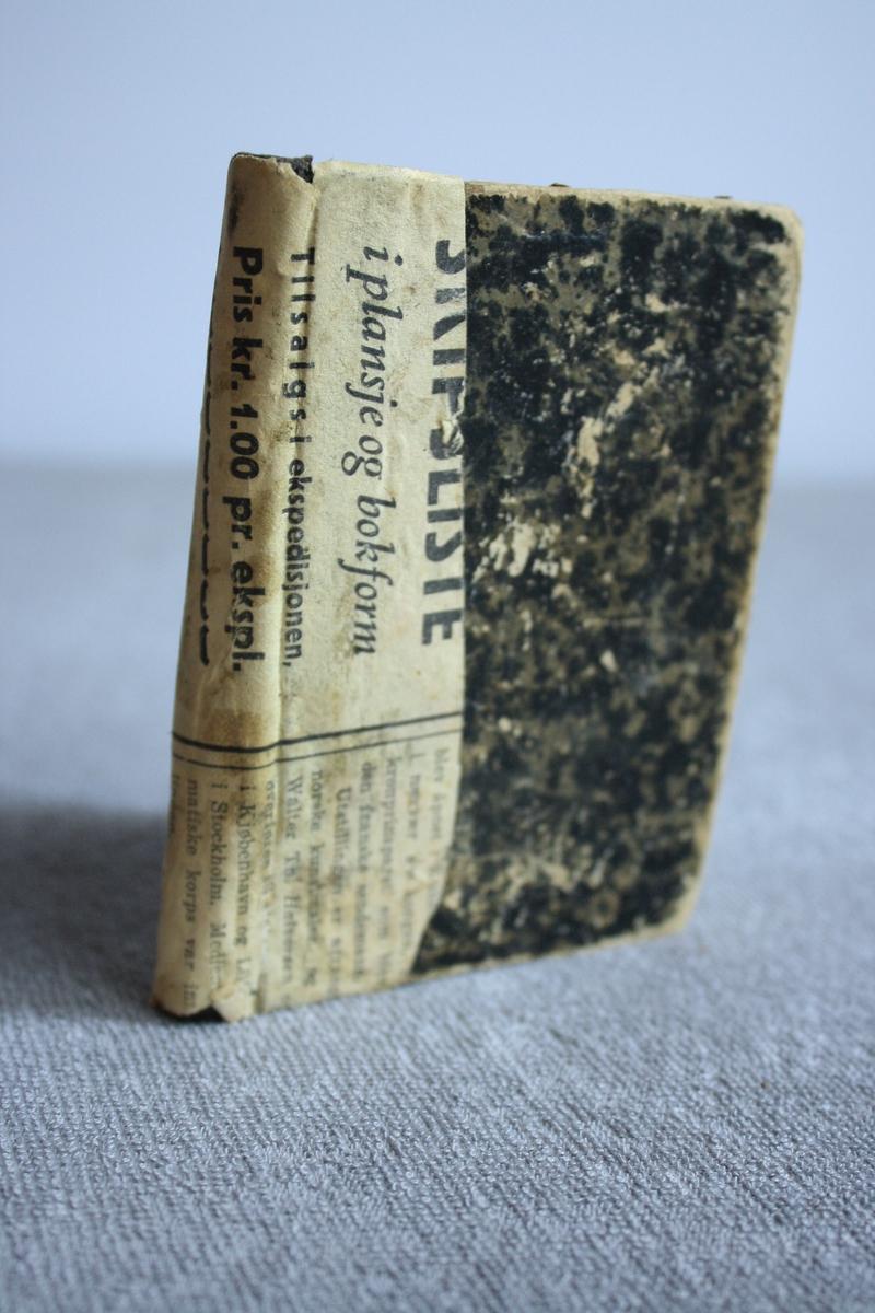 Bok med papp-perm i spraglete mønster. Rundt ryggen på permen er det limt fast eit stykke avispapir.