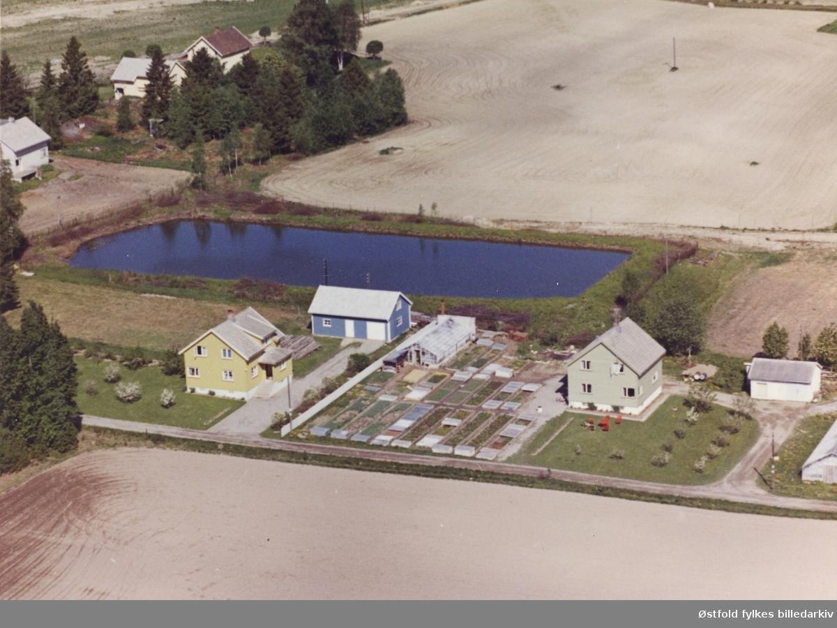 Flyfoto av gartner Rolf Thoresens eiendom i Meieribyen. Bolighus og gartneri i forgrunnen. I bakgrunen meieridammen hvor vannet til meieriet ble hentet fra, bak i det fjerne det da enda ubebyggede jordet på Koffeld søndre gnr.55/1.