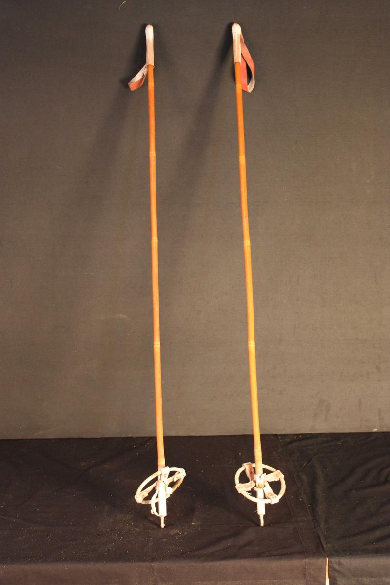 Bambusstavar med skinnhylse og reimer som handtak. Trinser av bambus og lær