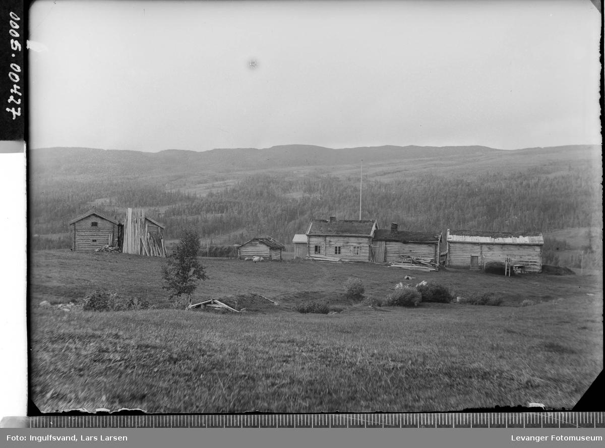 Oversiktsbilde av en gård med fjell i bakgrunnen.