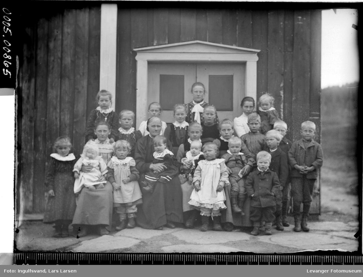 En forsamling av kvinner og barn foran et inngangsparti.