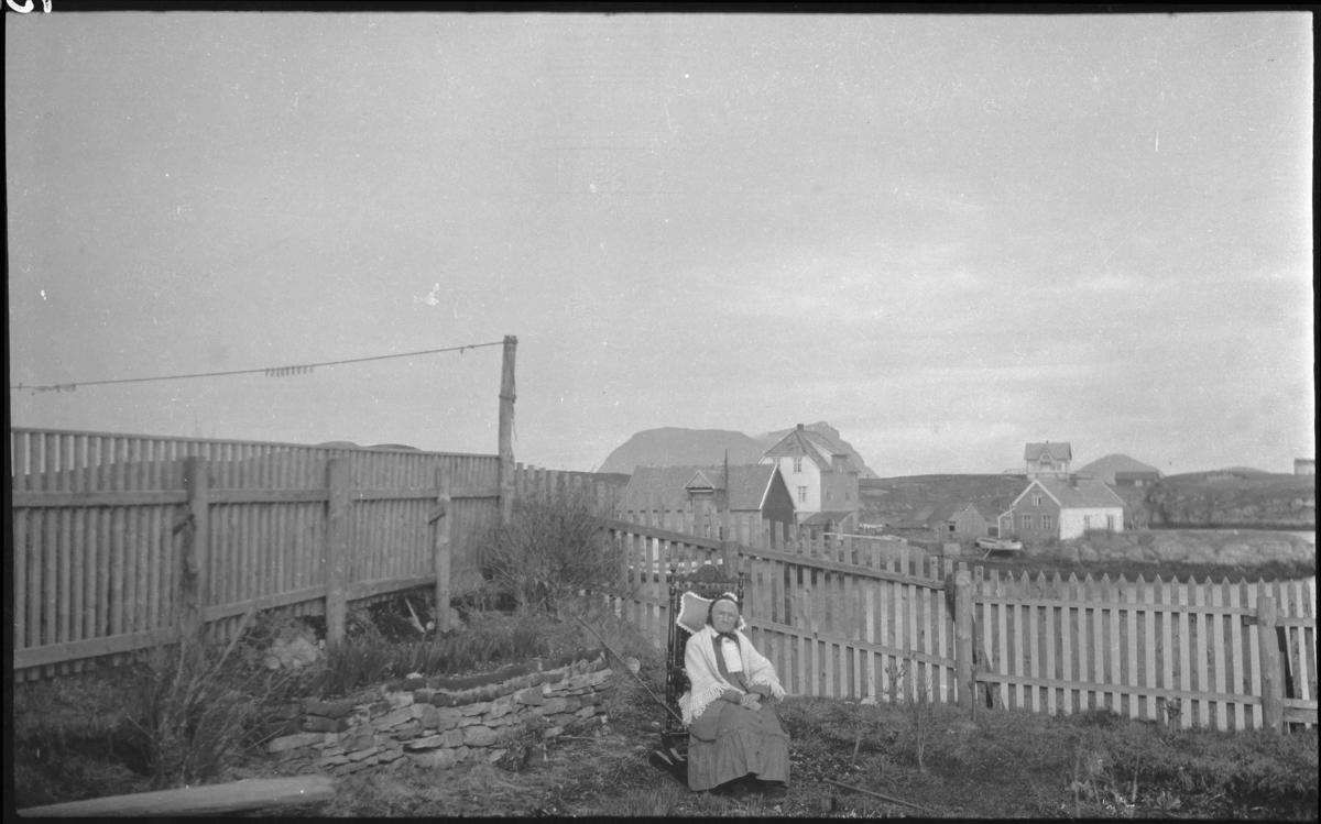 """Fru Nordstrand (gamla på Vadøyneset) i gyngestol i hagen. Husa på """"Skjæret"""" i bakgrunnen."""