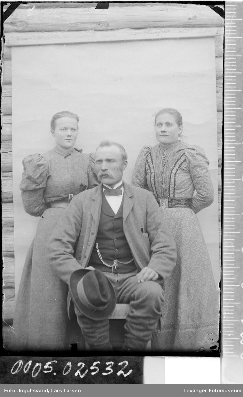 Gruppebilde av en sittende mann og to kvinner.