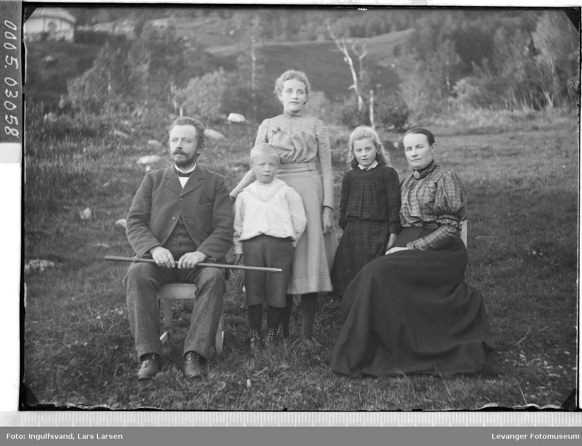 Gruppebilde av kvinne, mann og tre barn i helfigur.