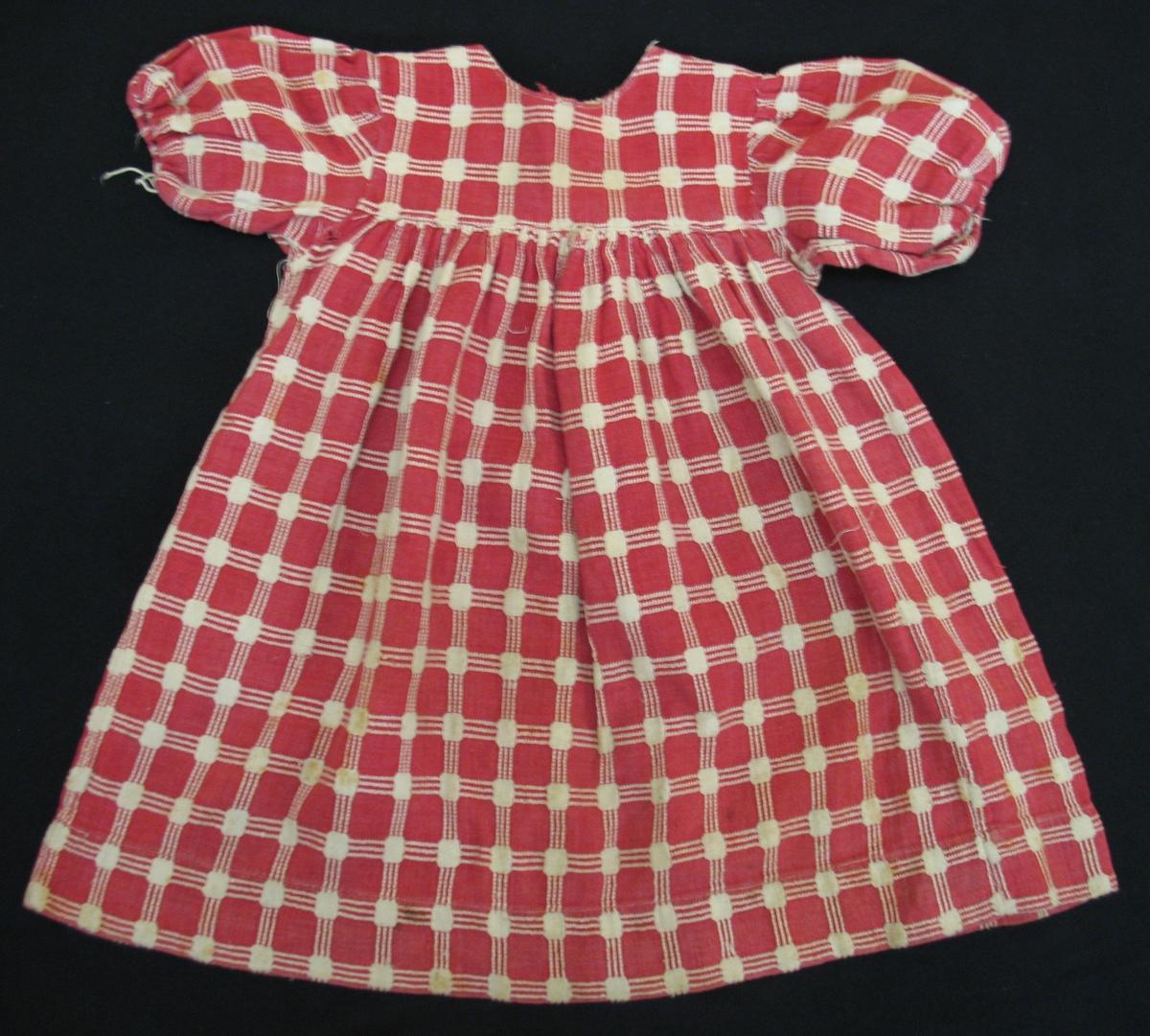 Barnklänning i röd och vitrutigt bomullstyg. Ok och puffärmar. Oket knäppt  baktill med tre cd9a1188626dc