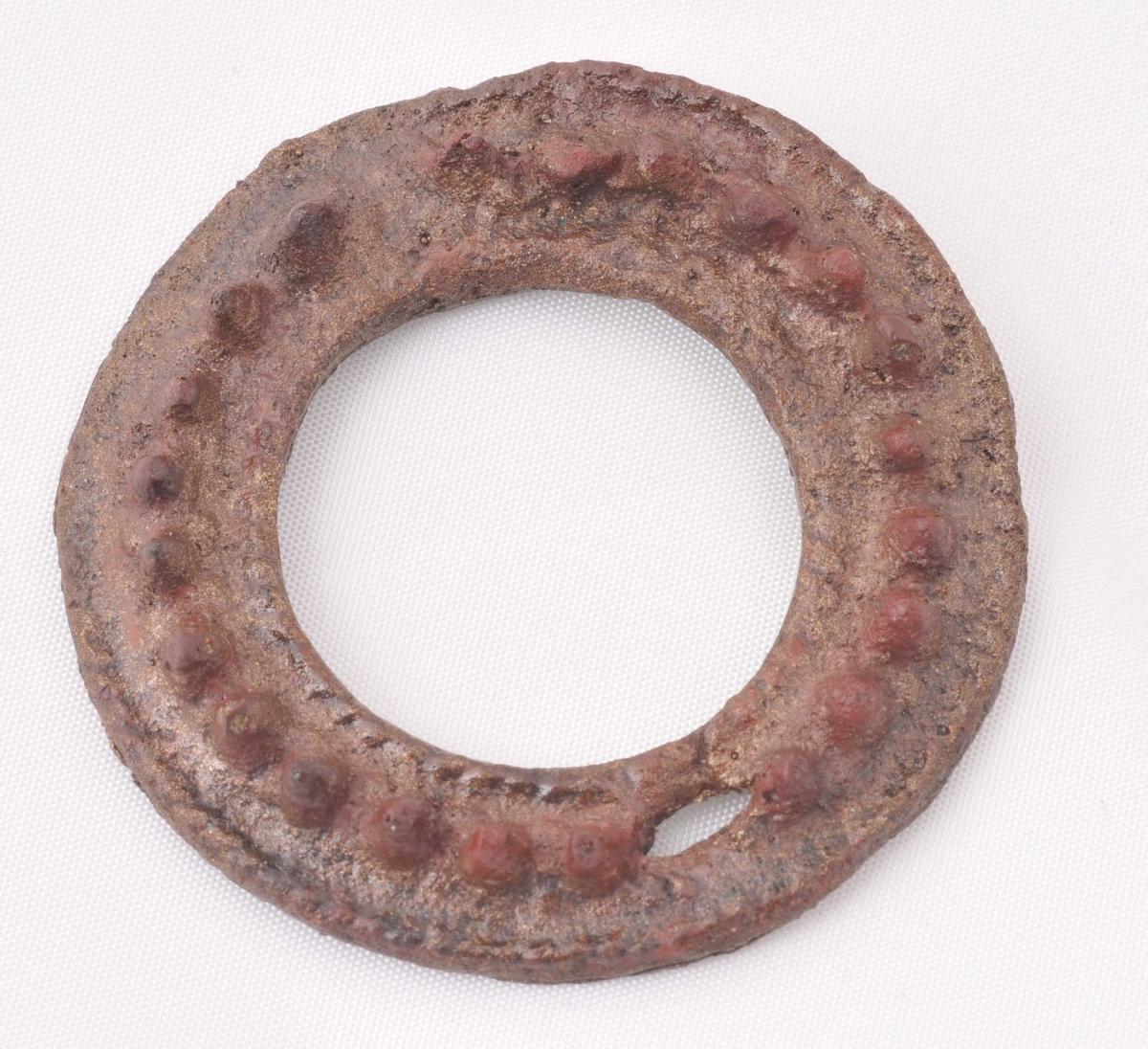 Rund, open ring med taggerand rundt. Kopi av original spenne.