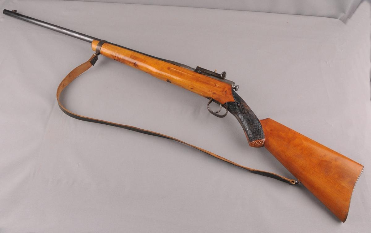Ei enkel heimegjort rifle. Lakkert tre. Kolbekappe i stål. Ruteskoren dekor på pistolgrepet. Enkel skulpeskurd på enden av pistolgrep. Gravering av rose på hevarmen. Har ein type fast dioptersikte. Rifla løp. Med lêrreim.