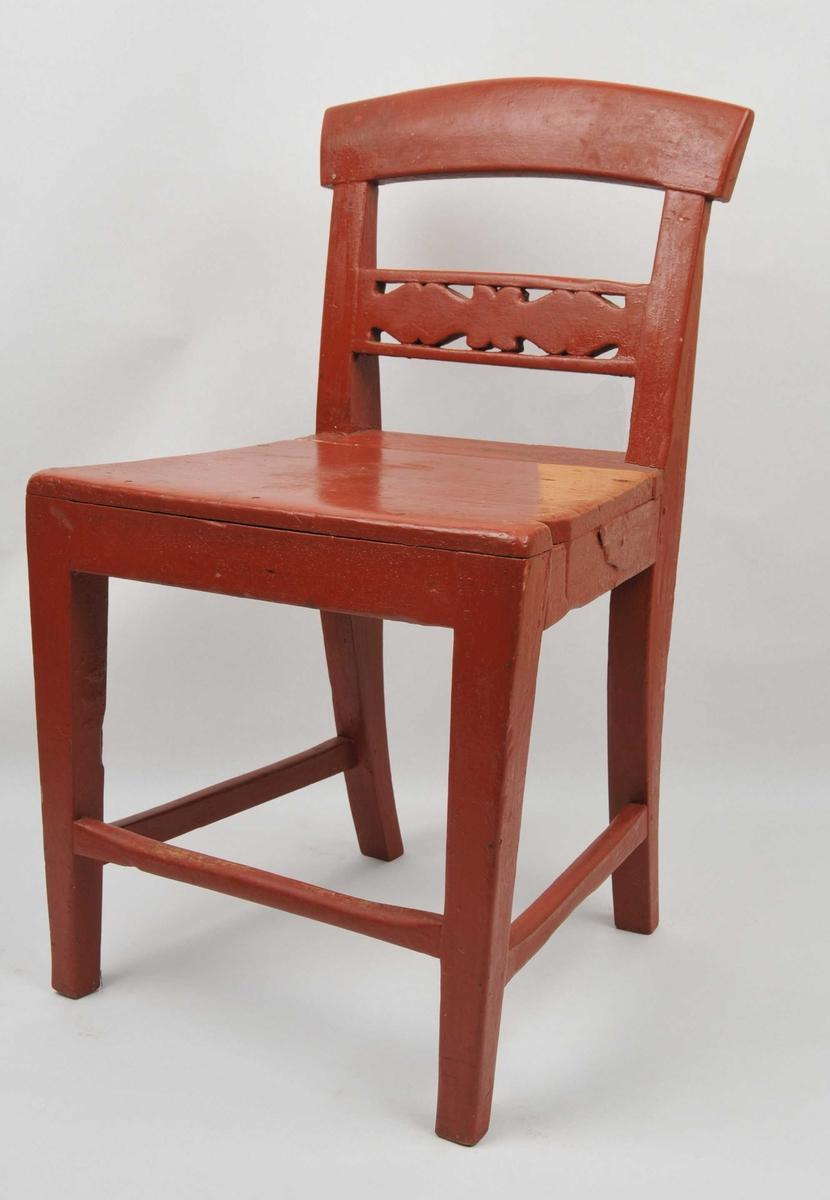 Raudmåla grindestol i bjørk. Ei spile i ryggen med gjennomskoren dekor. Overstykket på stolryggen svingar opp i ein boge. Fire bein med tverrspiler på kvar side og i front. Sprukken i setet.