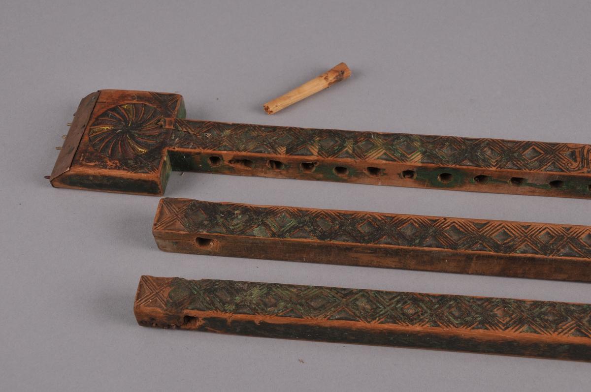 Vevspenne i tre, karveskurd langs heile spenna og med rosettar i kvar ende. Seks par jernpiggar i kvar einde. Restar etter grøn måling.