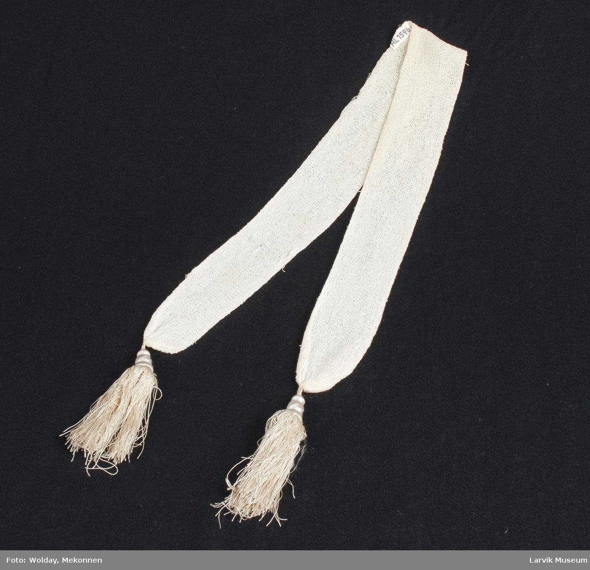 Form: tynt hvitt bom.garn,silkekvaster i endene,  håndstrikket i rette masker frem og tilbake ca. 5 r m pr. cm.,dobbelt lagt og sydd sammen bortsett fra 15 cm midtpå